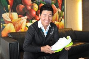 Ashun Wu holding a shoe.