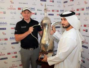 Gallacher with his Omega Desert Dubai Classic trophy.  Lets hope that if he wins this week, the photographer will ask everyone in the picture to look at the same camera...