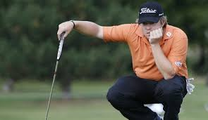 He isn't bored, he is just lining up a putt.  Concentration.